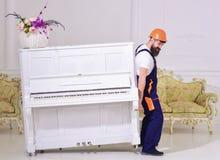 装载者移动钢琴仪器 传讯者交付家具,搬出,拆迁 有胡子工作者的人盔甲的和 库存照片