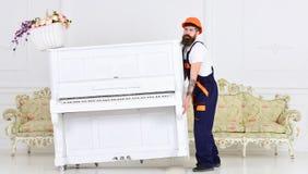 装载者移动钢琴仪器 有胡子工作者的人盔甲和总体的提起,努力移动钢琴,白色 库存照片