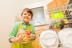 装载肮脏的盘的愉快的孩子男孩对洗碗机 免版税库存图片