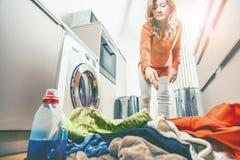 装载肮脏的衣裳的妇女装货洗涤的machineWoman在洗涤物的洗衣机 免版税库存图片