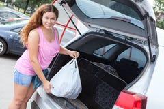 装载袋子的桃红色衣裳的可爱的少妇在suv 免版税库存图片