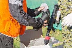 装载迷彩漆弹运动枪的两个人用球户外 免版税库存图片