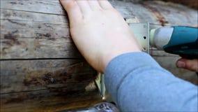 装配一个木制框架和修建房子 俄国 工作者螺丝螺丝到与螺丝刀的被预演练的孔里 股票录像