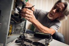 装配一台台式计算机的老人 免版税库存图片