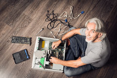 装配一台台式计算机的老人 免版税库存照片