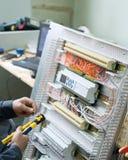 装配低压工业HVAC控制箱的技术员在车间 特写镜头照片 免版税库存照片