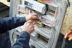 装配低压的技术员装配工业HVAC控制板在车间 手的特写镜头照片 库存图片