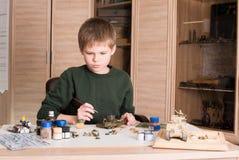 装配和绘塑料式样坦克的青少年的男孩在工作场所 免版税库存照片