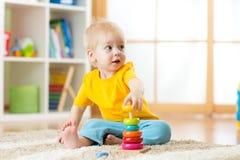 装配在地板上的逗人喜爱的孩子男孩画象五颜六色的金字塔玩具在客厅 库存照片