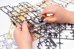 装配塑料模型的男孩的手使用工具 库存照片