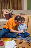 装配家的父亲和儿子一套新的家具 免版税库存图片