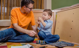装配家的父亲和儿子一套新的家具 免版税图库摄影