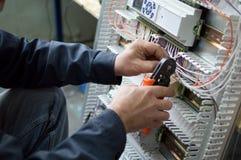 装配工业HVAC控制台室的电工的手在车间 特写镜头照片 免版税库存图片