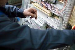 装配工业HVAC控制台的电工的手在车间 特写镜头照片 库存图片