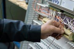 装配工业HVAC控制板的电工在车间 特写镜头照片 免版税库存图片