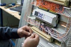 装配工业HVAC控制箱的电工的手在车间 特写镜头照片 免版税图库摄影
