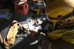装配工人在起重机的书面配置安全率容量水平卷扬机举的计划在使用之前 库存照片
