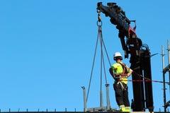 装配工人帮助起重机,保留正确的平衡和方向 免版税库存照片