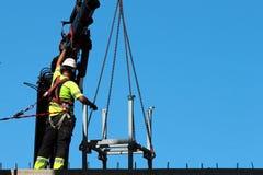 装配工人帮助起重机,保留rigth平衡和方向 库存图片