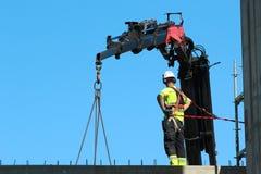 装配工人帮助起重机,保留rigth平衡和方向 图库摄影