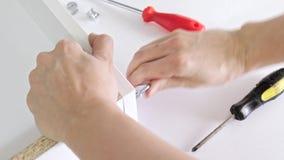 装配新的白色抽屉的接近的观点的人使用螺丝刀,拧紧有一个六角形的艾伦键的一个螺丝 股票视频