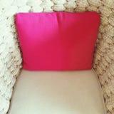 装饰一把米黄扶手椅子的桃红色坐垫 免版税图库摄影