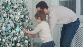 装饰与中看不中用的物品的父亲和儿子圣诞树在客厅 图库摄影