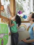装饰与保险开关图画的老师和女孩窗口 免版税库存照片