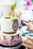 装饰与花的有排列的乳香树脂除草蛋糕和上色由刷子的细节 库存图片
