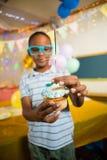 装饰与闪烁发光物的逗人喜爱的男孩杯形蛋糕在生日聚会期间 免版税库存照片