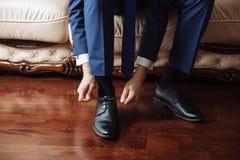 装饰与经典,典雅的鞋子的商人 修饰佩带在婚礼之日,栓鞋带和准备 免版税库存图片