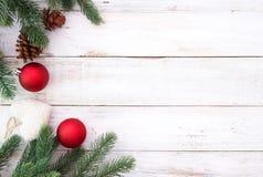 装饰元素和装饰品的圣诞节土气在与雪花的白色木桌上 库存照片