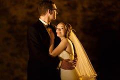 装饰典雅的时尚新郎和新娘在后面拥抱 库存图片
