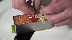 装饰剁碎的三文鱼的厨师手形成在小金属型关闭在现代餐馆 准备鱼的厨师 股票录像