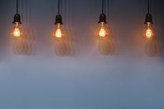 装饰古色古香的反对墙壁背景的爱迪生样式电灯泡 免版税库存照片