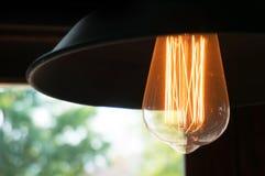 装饰古色古香的反对窗口视图的爱迪生样式电灯泡 图库摄影