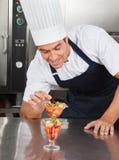 装饰可口点心的年轻厨师 库存图片