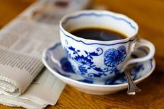 装饰咖啡杯在与报纸的木桌里 库存图片