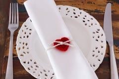 装饰圣徒情人节:有手工制造红色钩针编织心脏的白色板材餐巾叉子刀子 免版税库存图片