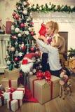 装饰圣诞树和准备礼物的小女孩 免版税库存图片
