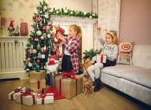 装饰圣诞树和准备礼物的小女孩 免版税图库摄影