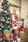 装饰圣诞树和准备礼物的小女孩 库存照片