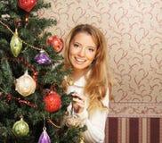 装饰圣诞树的一个十几岁的女孩 免版税库存图片