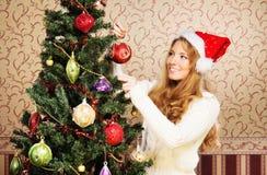 装饰圣诞树的一个十几岁的女孩 免版税图库摄影
