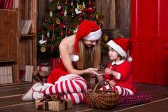 装饰圣诞树的两个圣诞老人女孩获得乐趣 新年内部 Xmas大气,庆祝假日的家庭 免版税库存照片