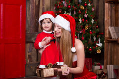 装饰圣诞树的两个圣诞老人女孩 新 免版税库存照片