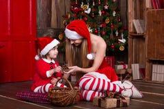 装饰圣诞树的两个圣诞老人女孩 新 图库摄影