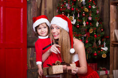 装饰圣诞树的两个圣诞老人女孩 新 库存图片
