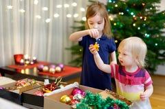 装饰圣诞树的两个妹 免版税库存图片