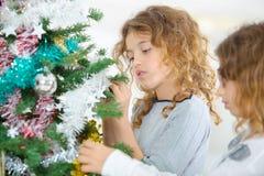 装饰圣诞树的两个姐妹 免版税图库摄影